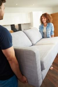 Couple Carrying Sofa As They Move Into New Home
